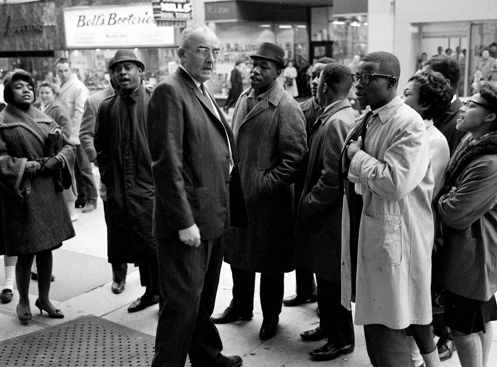 A Wilson-Quick Pharmacy official, center, attempts to talk with a small group of black and white students as they sing during their sit-in demonstration at the downtown store Jan. 6, 1962. One of the demonstrators is Catherine Burks, left.