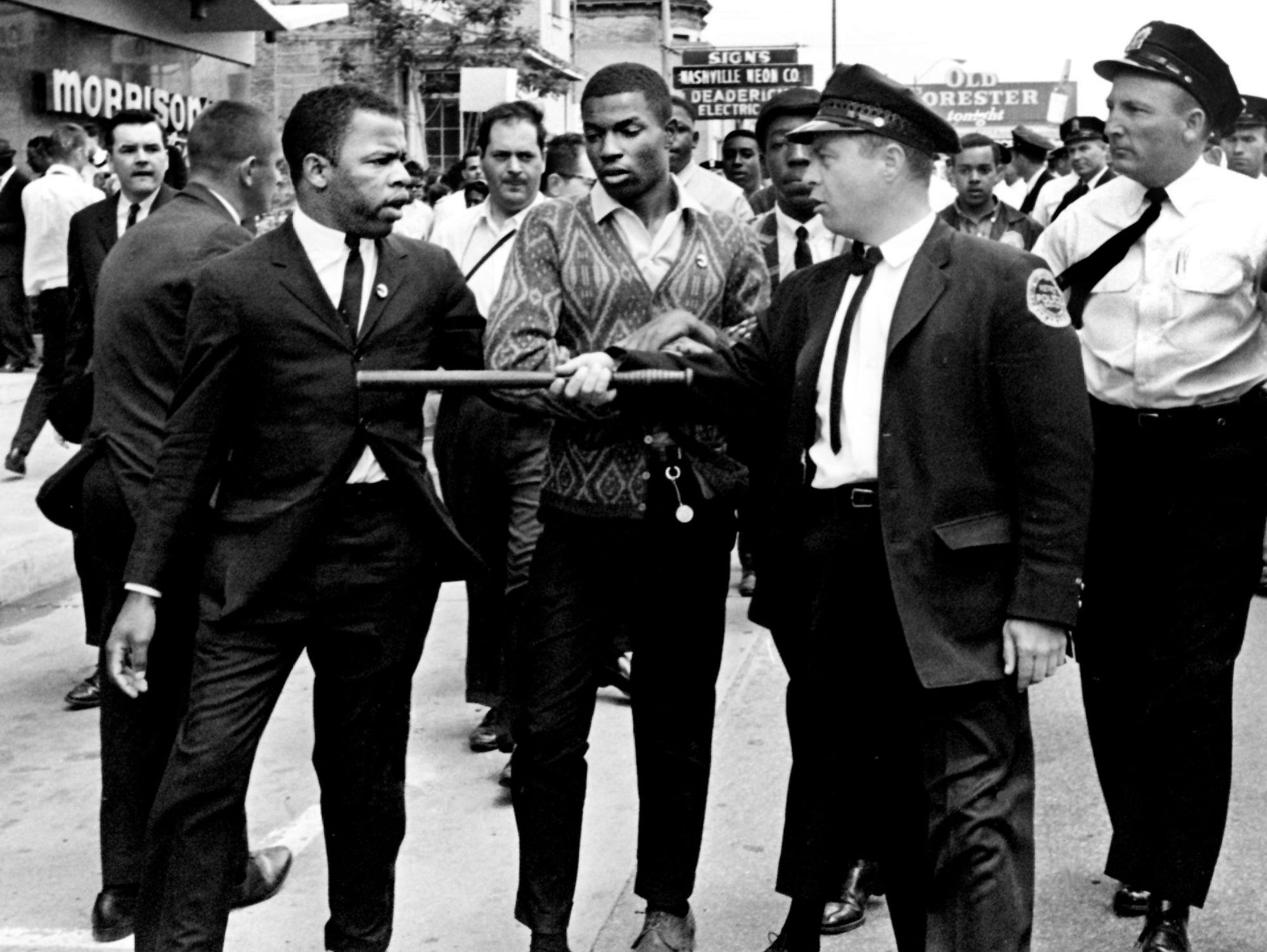 A Metro police officer points his stick at John Lewis, left, one of the leaders of the civil rights demonstrators, at Morrison's Cafeteria on West End Avenue on April 29, 1964.