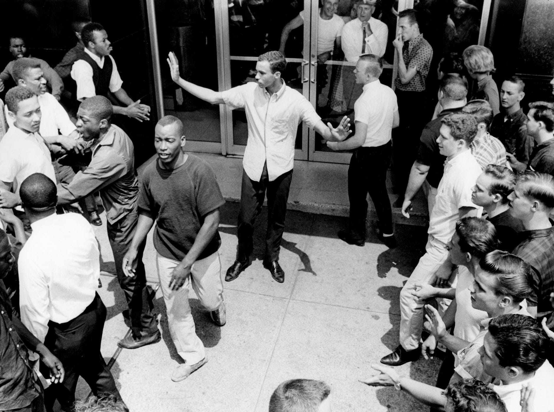 A black leader, center, tries to keep his group separated from a group of white youths near Cross Keys Restaurant downtown May 10, 1963. The black groups were holding sit-in demonstrations at the restaurant as well as the B & W Cafeteria.