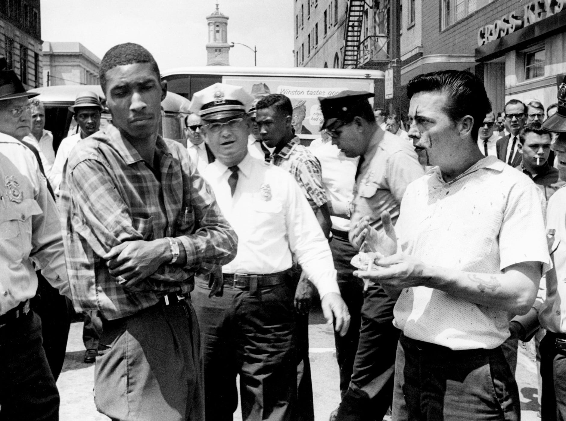 Metro police arrest a marcher and a downtown spectator after a scuffle developed during a demonstration May 8, 1963. Joseph Frank Tanksley, right, was cut after falling into a mirror beside Cross Keys Restaurant. Tanksley and Vencen Horsley, left, were charged with fighting and disorderly conduct. Lt. C.P. Lynch, center, was the arresting officer.