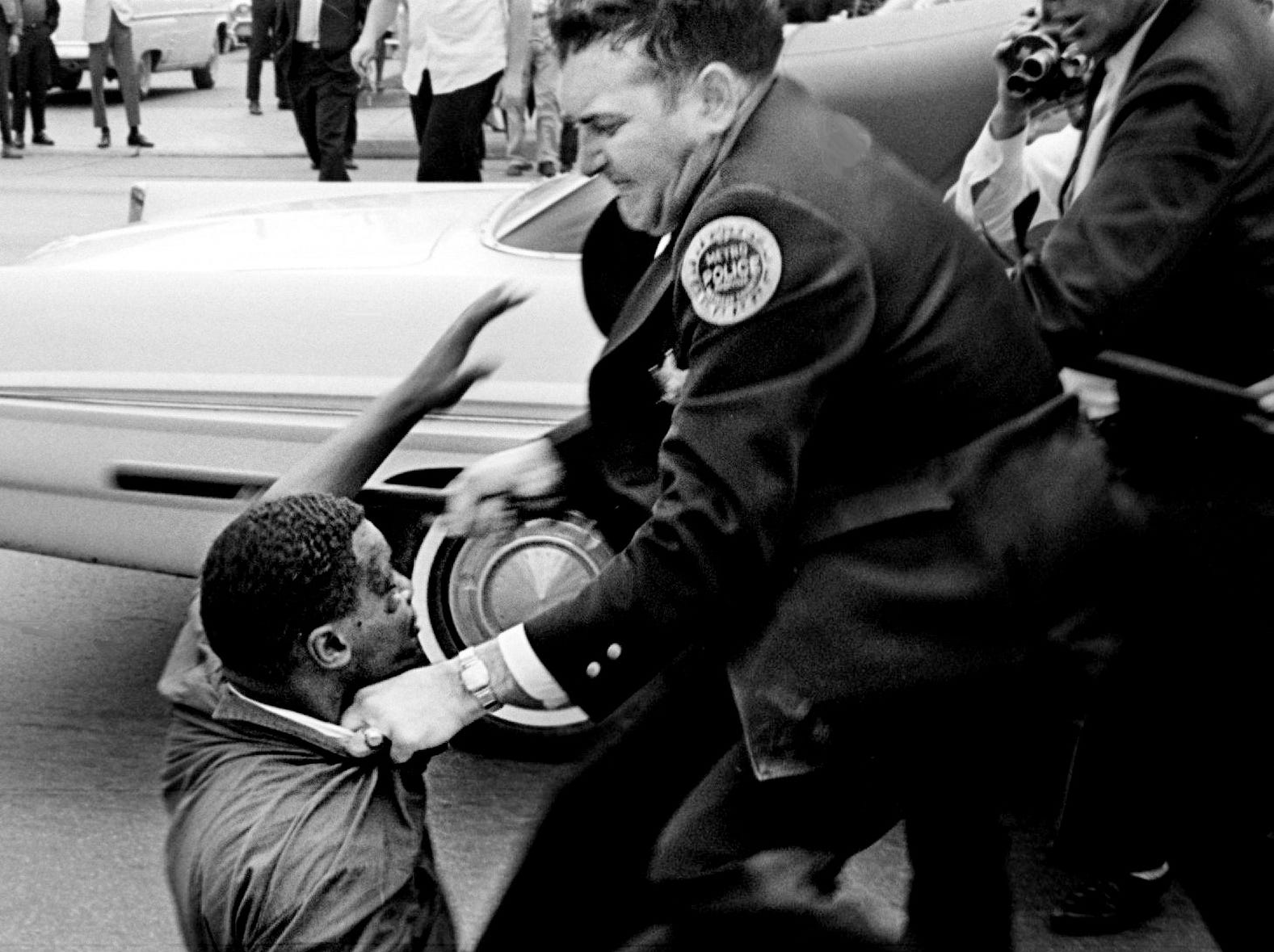 Metro patrolman J. W. Vanatta wrestles civil rights demonstrator Lester McKinnie down to the ground on West End Avenue in front of Morrison's Cafeteria on April 27, 1964.