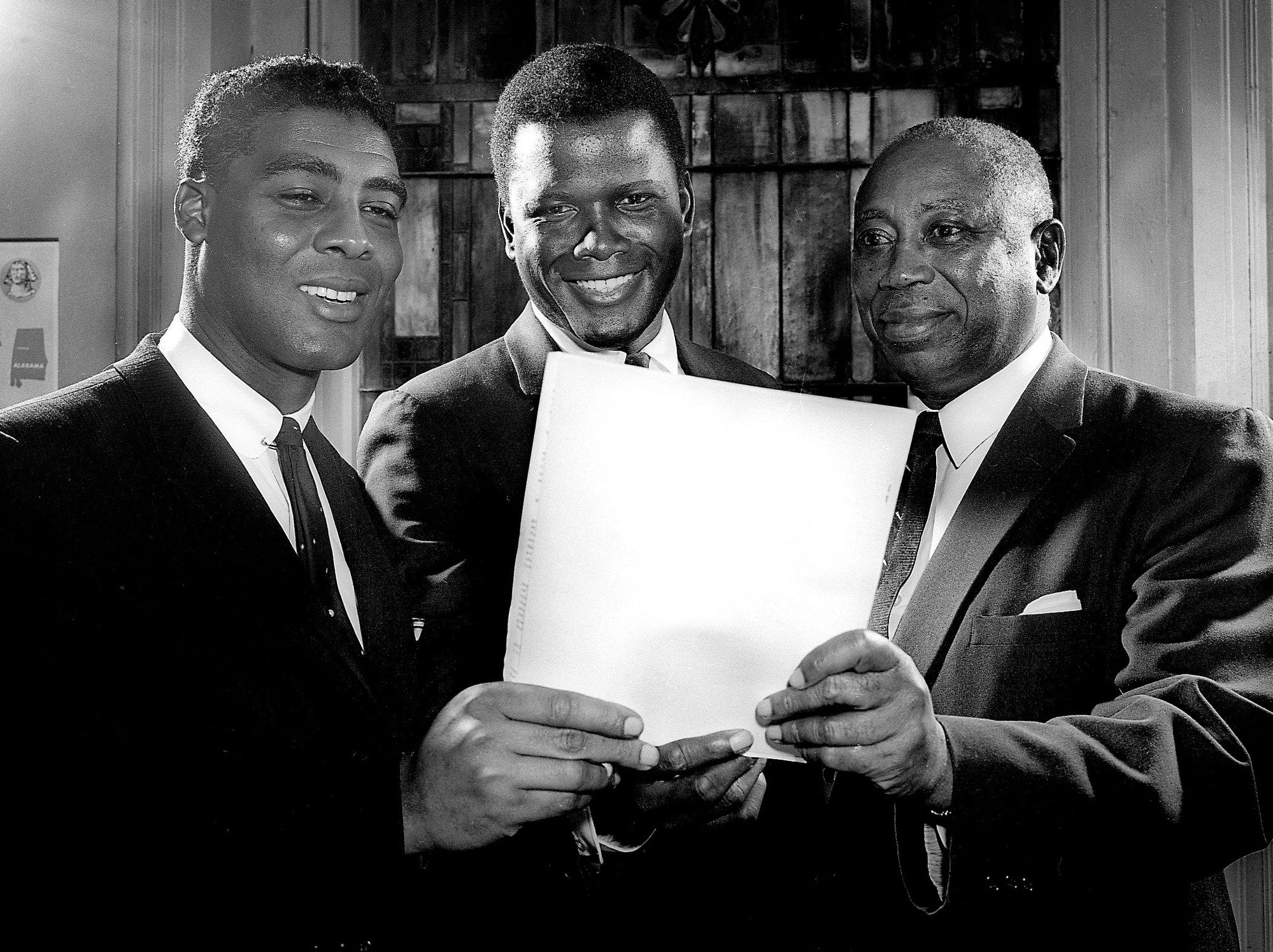 Black leaders explain to actor Sidney Poitier, center, plans for a fundraising drive to finance the Nashville Christian Leadership Council's work. The Rev. Kelly M. Smith, left, council president, and Dr. Matthew Walker Sr., campaign chairman, talk with the actor before he addressed a rally March 4, 1962.