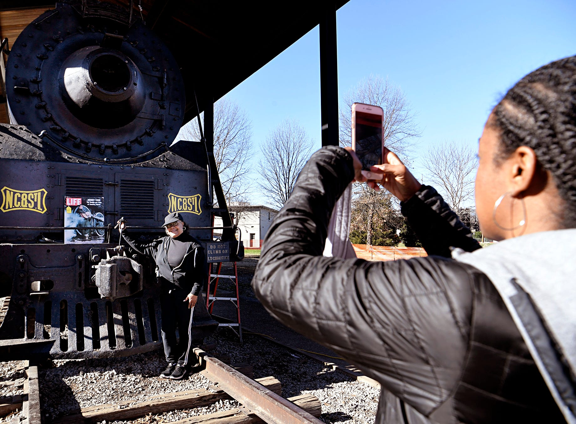 Jeri Shull takes a photograph of her aunt, Jackie Eslick, in front of steam locomotive  No. 576  at Centennial Park in Saturday, Jan. 6, 2019.