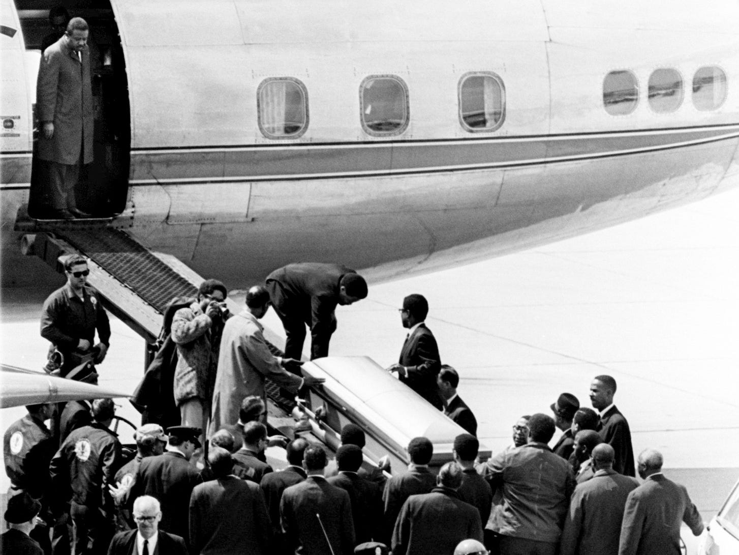 Dr. Ralph Abernathy, successor to the Rev. Martin Luther King Jr. as head of the Southern Christian Leadership Conference, stands at the top of the ramp as pallbearers lift the slain civil rights leader's casket aboard an Atlanta-bound plane April 5, 1968.