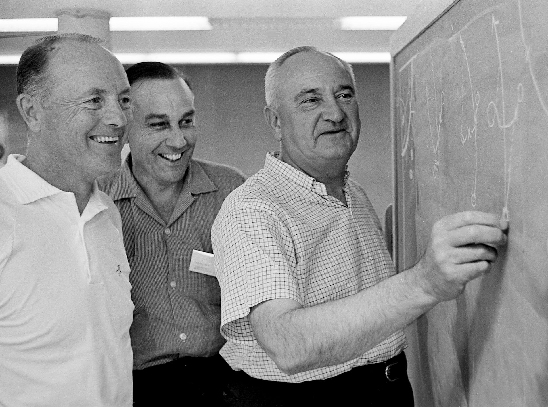 Here's the way Kentucky works its basketball offense, Adolph Rupp, right, tells Tennessee offensive football coach Harvey Robinson, left, and Norvall Neve, commissioner of the Missouri Valley Conference at the Blue Ribbon Coaching Clinic at Tennessee State A&I Aug. 1, 1962.