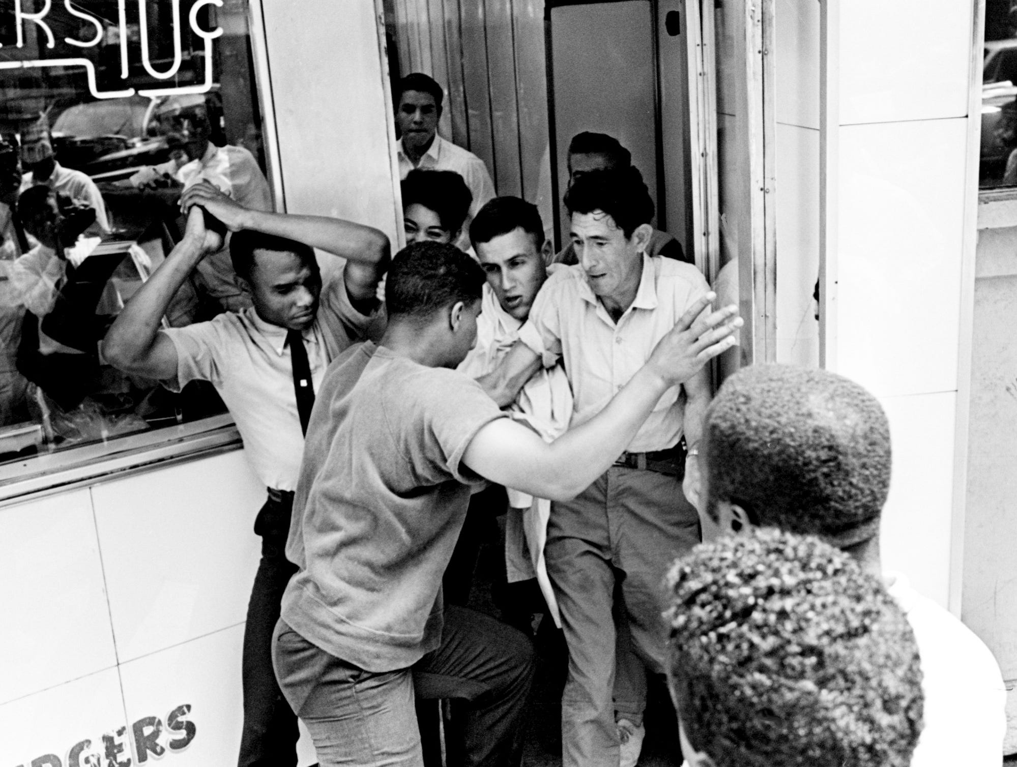 A couple of civil rights demonstrators, left, get pushed out the door by Tic Toc Restaurant employees and white customers in their attempt to get served May 11, 1964.
