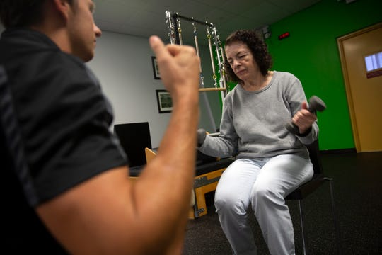 Bella Appelman, who has Parkinson's disease, does arm curls with trainer Lee Pinkham on Thursday, Jan. 10, 2019, at Naples Personal Training in North Naples.