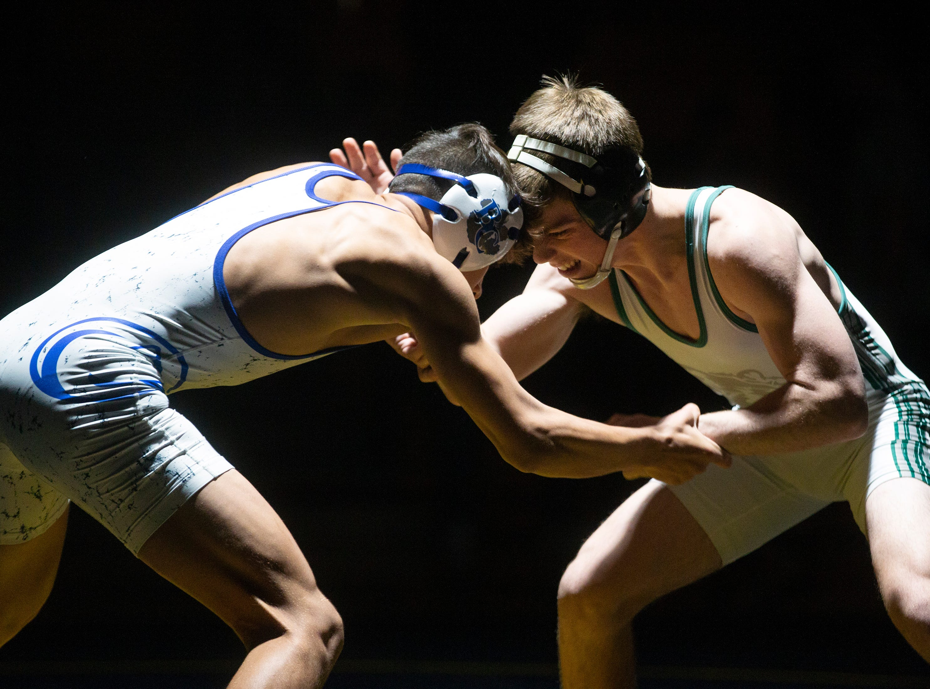 Barron G. Collier High School's Roy Chiong, left, takes on Palmetto Ridge High School's Ben McCallister in the 120-pound match up during the Collier County Athletic Conference wrestling championship, Wednesday, Jan. 9, 2018, at Naples High School.