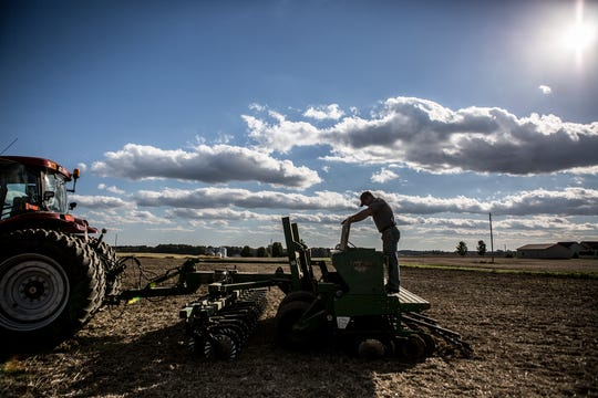 Andy Hollenback checks to make sure there is enough seed to finish planting a wheat field.