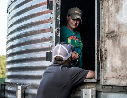 Andy and Mamie share a moment at one of their grain bins as Mamie sweeps the last bit of corn into a pile so it can be moved into their semi and hauled to the grain elevator.