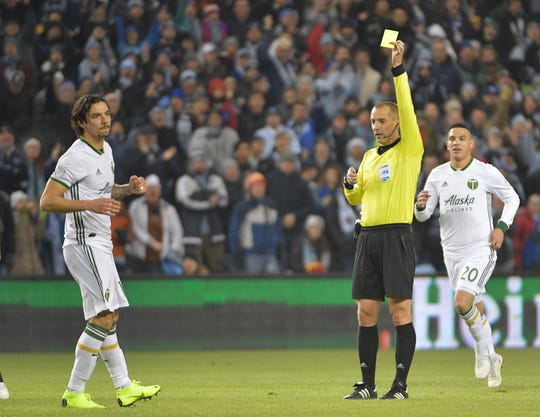 Nov 29, 2018; Kansas City, KS, USA; Portland Timbers defender Zarek Valentin (16) receives a yellow card from referee Mark Geiger in a match against Sporting Kansas City in the second leg of the MLS Western Conference Championship at Children's Mercy Park.