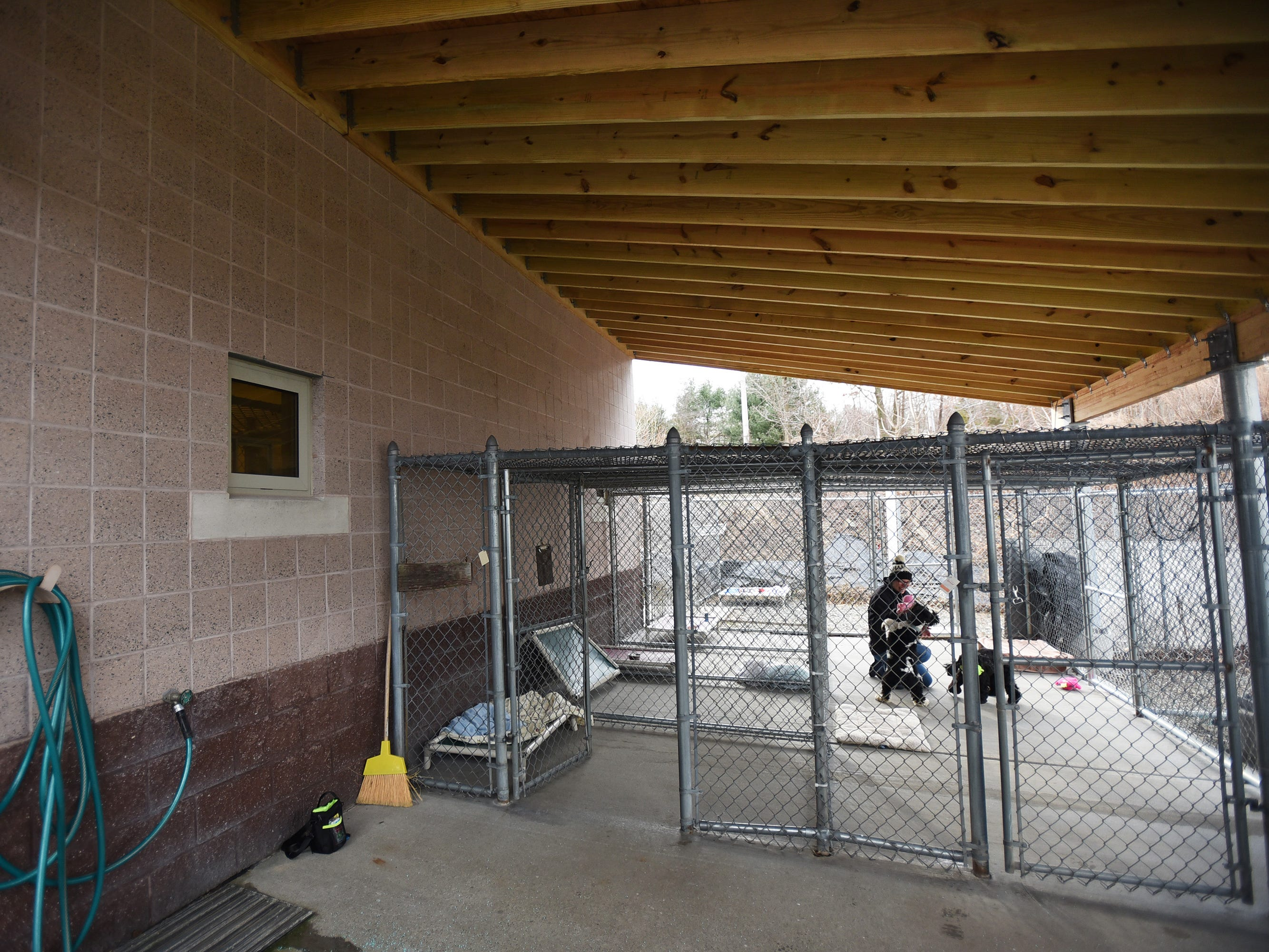 Senior Kennel Attendant Jeni Meehan, interacts with two adoptee dogs beneath a new roofed structure over the outdoor kennels, which was donated by Ridgewood Eagle Scout Frank Orlando, at Ramapo-Bergen Animal Refuge in Oakland on 01/10/19.