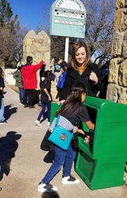 Angie Martinez helps a K-Kids student fill a Si Se Puede box with supplies.