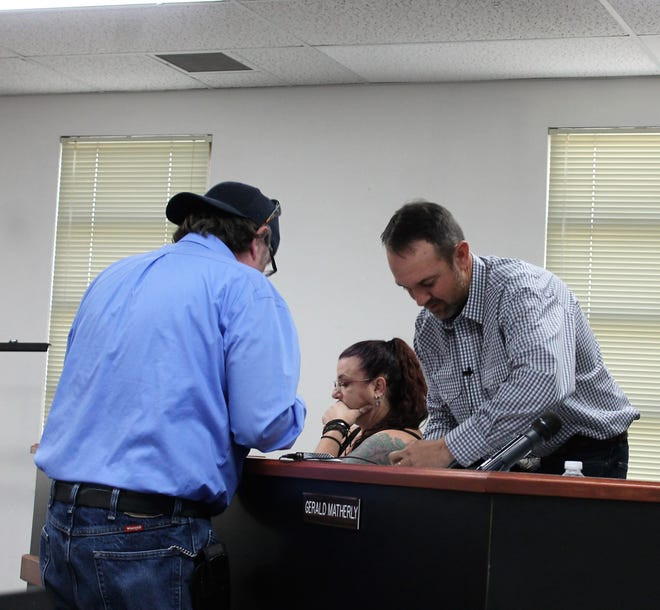Newly named Otero County Commission Chairman Couy Griffin, right, and former Otero County Commission Chairwoman Lori Bies, left, change places on the dais at Thursday's regular Otero County Commission meeting.