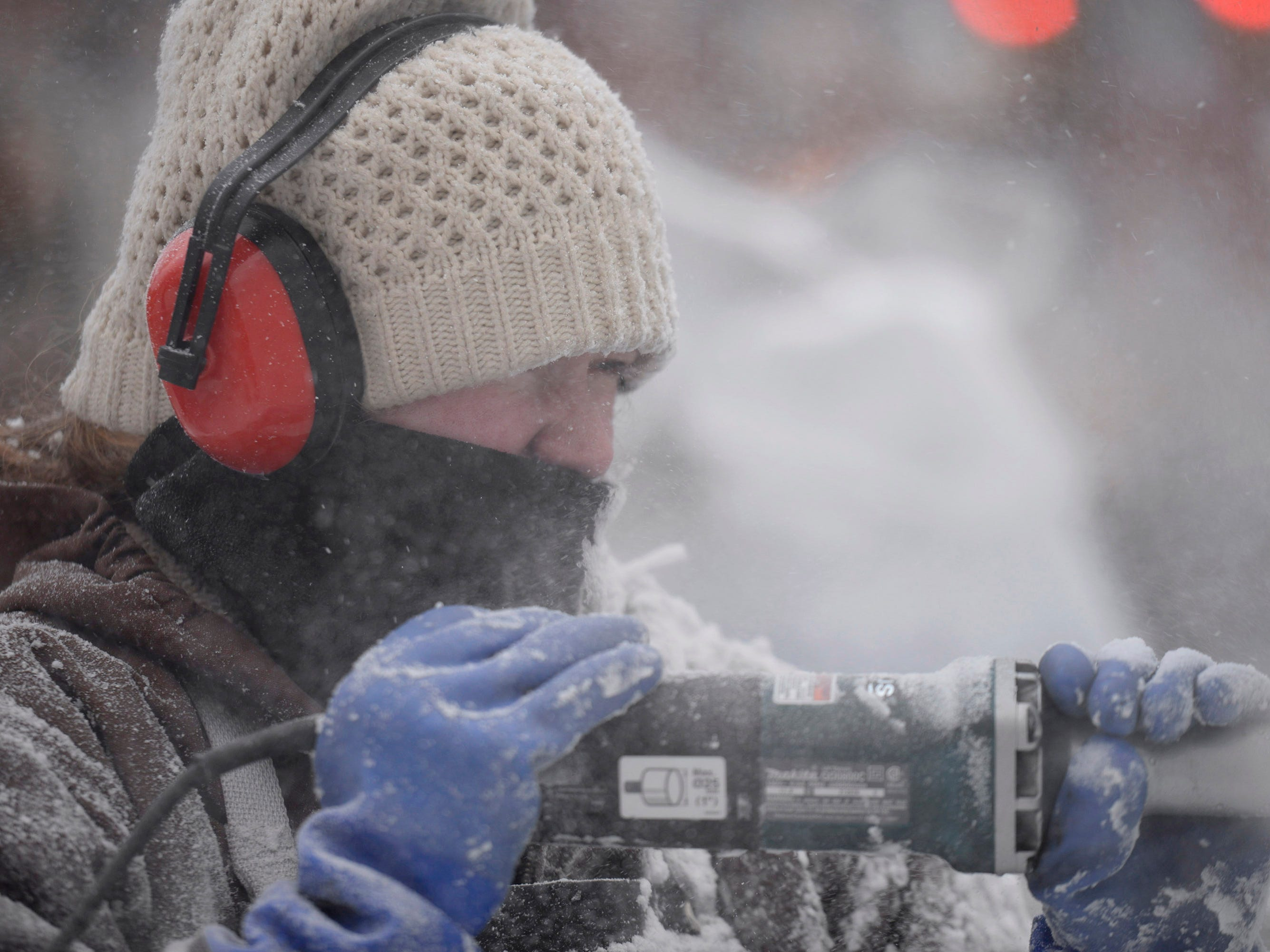 Lauren Klapar from Clear Cut Ice is all bundled up while she carves at the Plymouth Ice Festival that runs Jan. 11-13.