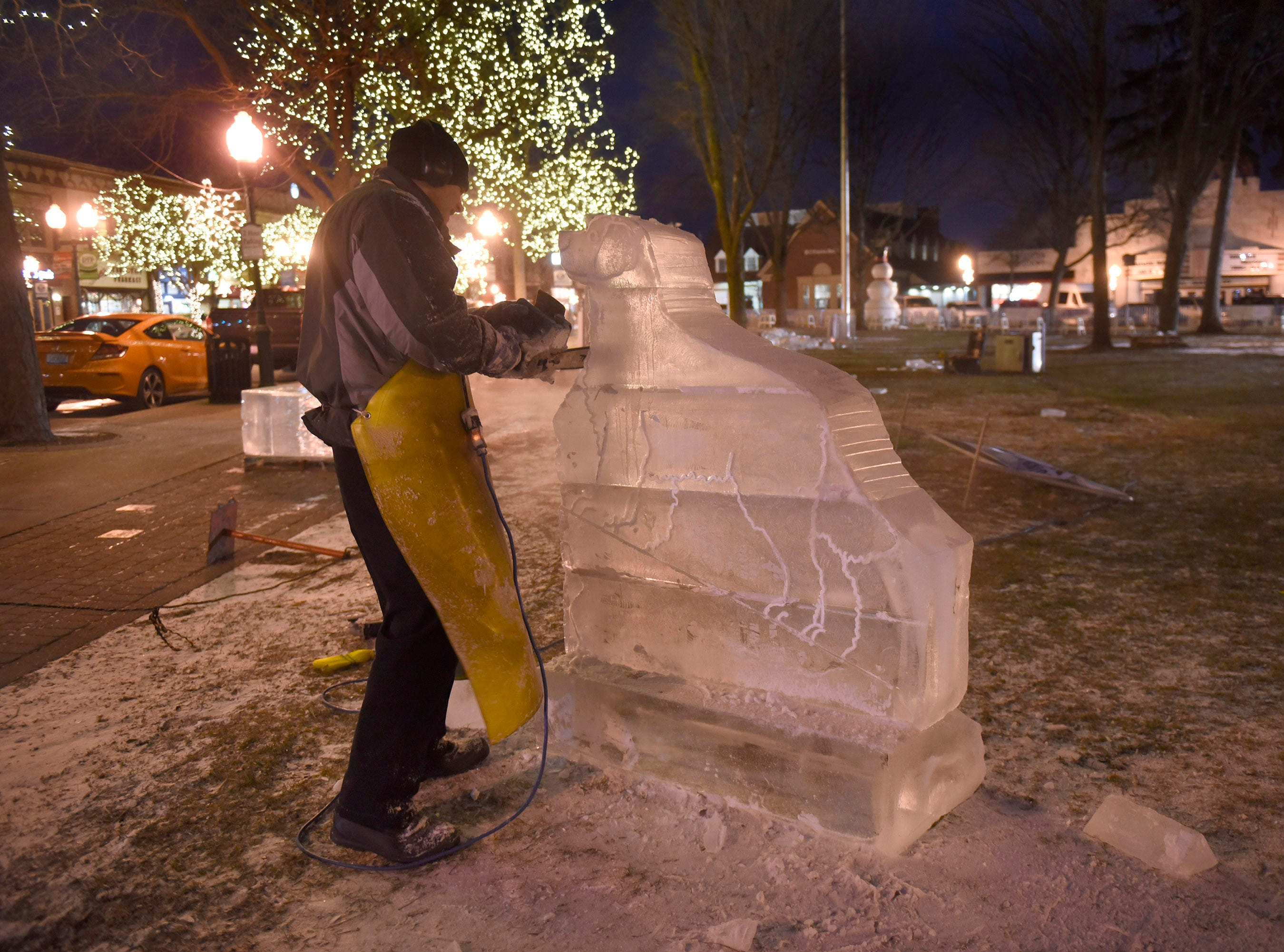 Clinton Rich works on a piece Wednesday evening in Kellogg Park that will become part of the Plymouth Ice Festival that runs Jan. 11-13.