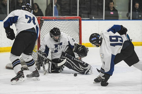 Farmington United goalie Justin Rogers makes the stop in front of teammates Matt Nieman (21) and Kyle Lawson (19).