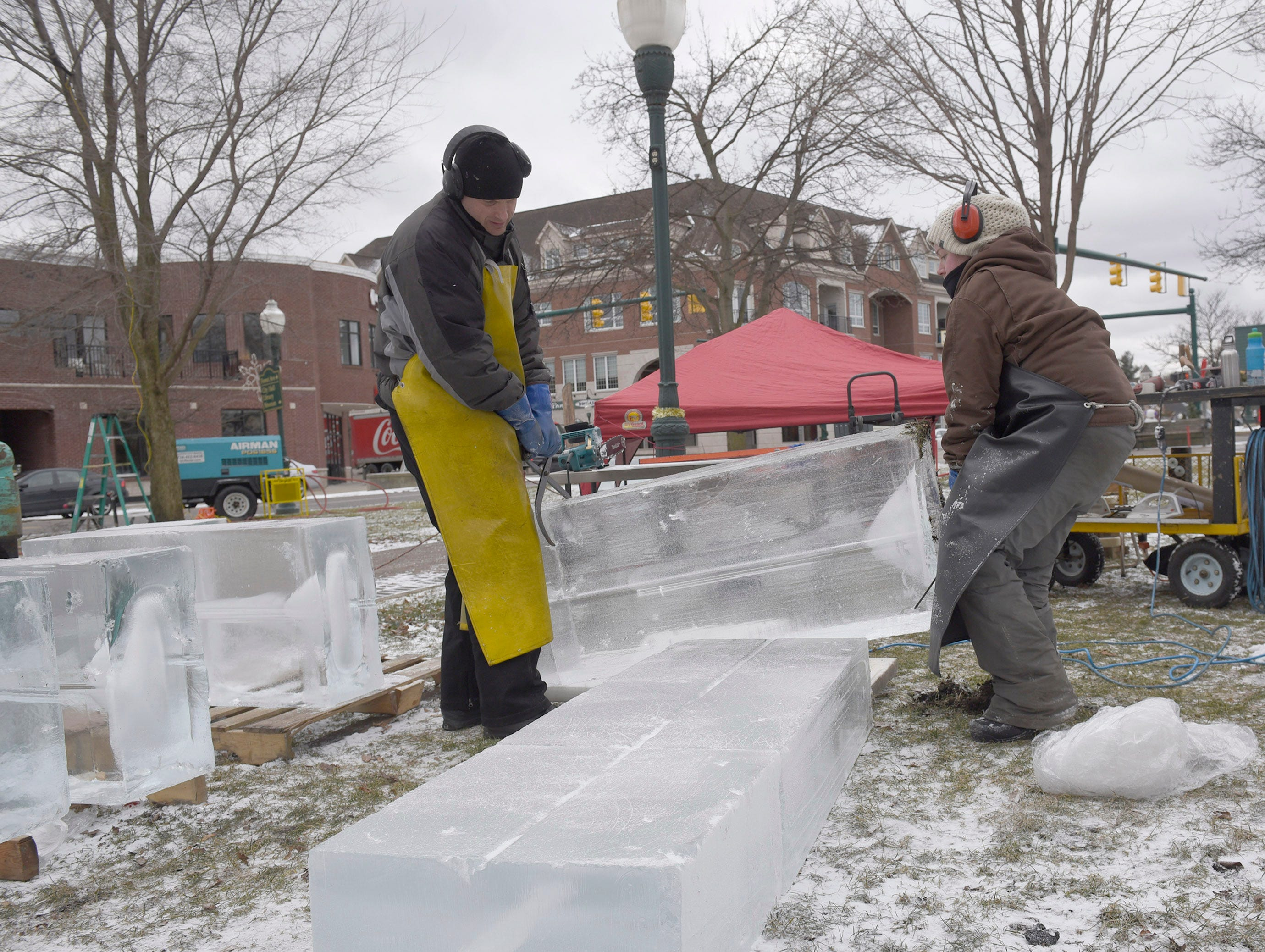 Clinton Rich (left) and Lauren Klapar set blocks of ice for sculptures that will featured during the Plymouth Ice Festival that runs Jan. 11-13.