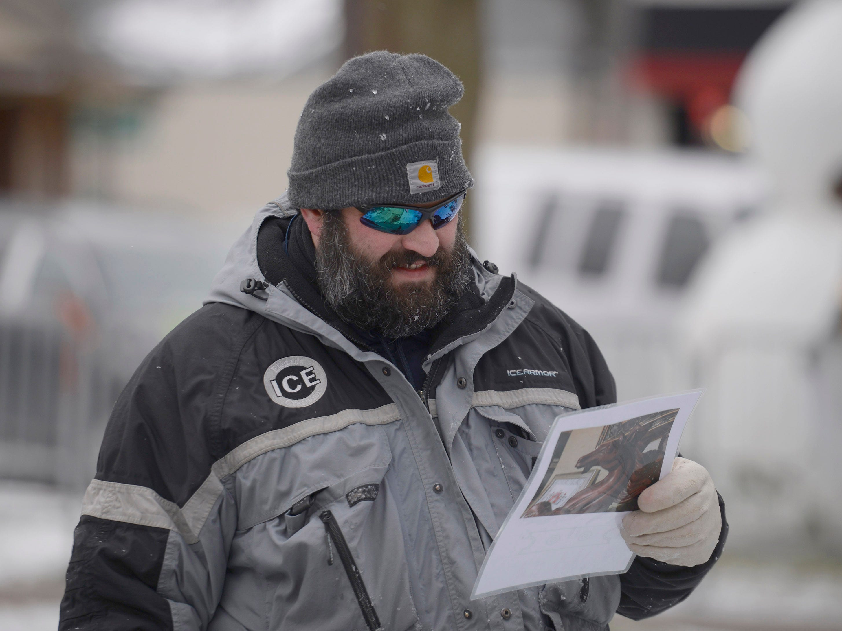 Ice carver Jeff Meyers looks over a blueprint for a sculpture at the Plymouth Ice Festival that runs Jan. 11-13.