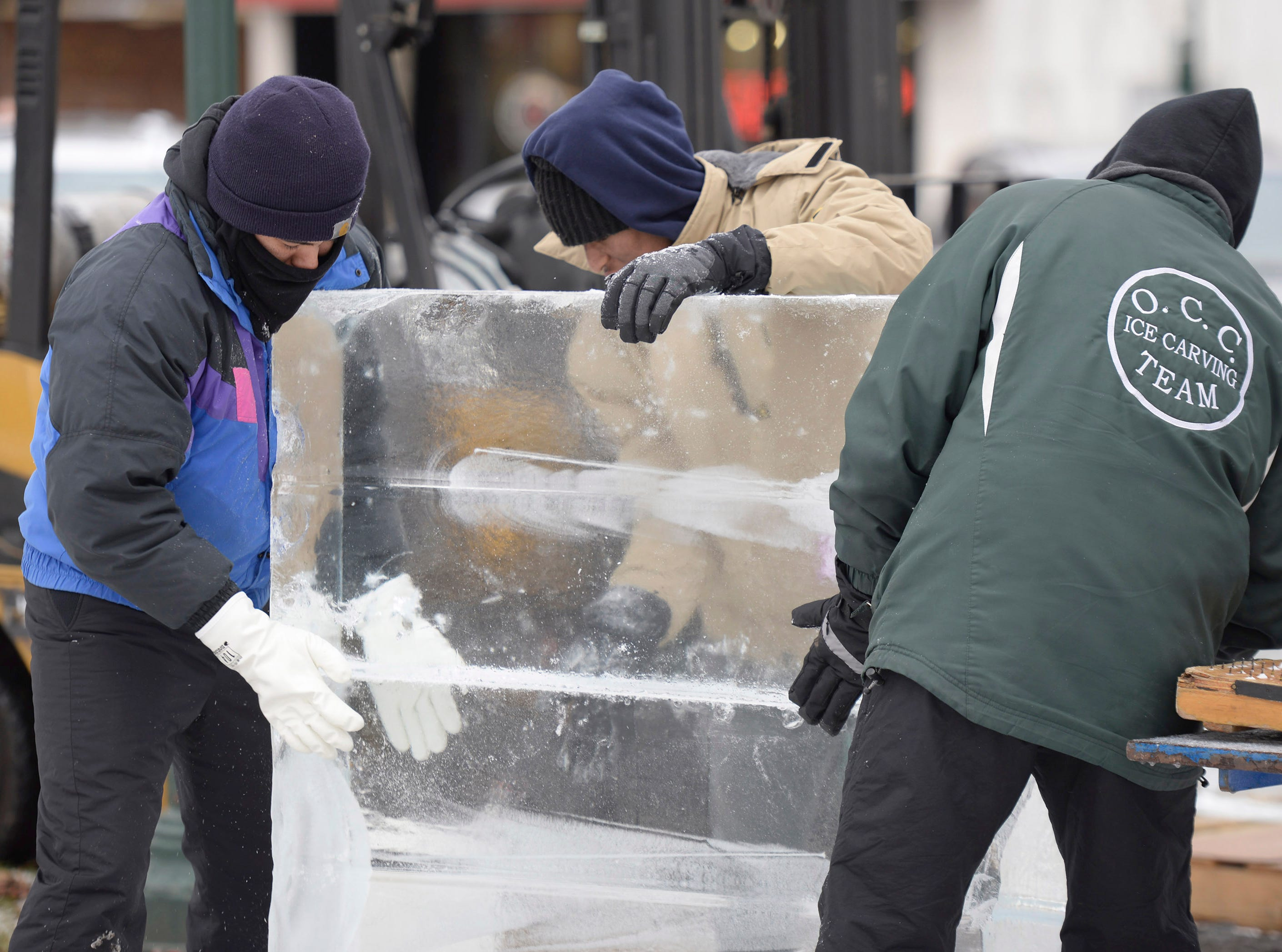 Brett Fuqua (left), Robert Williams and Aaron Whitten working for Elegant Ice Creations setting more than 80 blocks of ice that will become 11 sculptures at the Plymouth Ice Festival that runs Jan. 11-13.