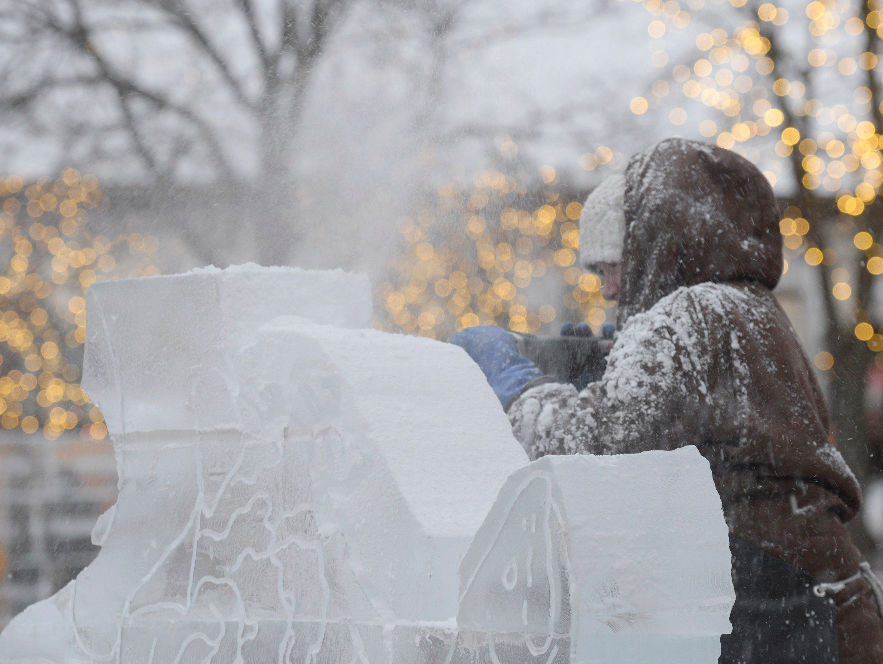 Lauren Klapar from Clear Cut Ice works on an ice carving in Kellogg Park for the Plymouth Ice Festival that runs Jan. 11-13.