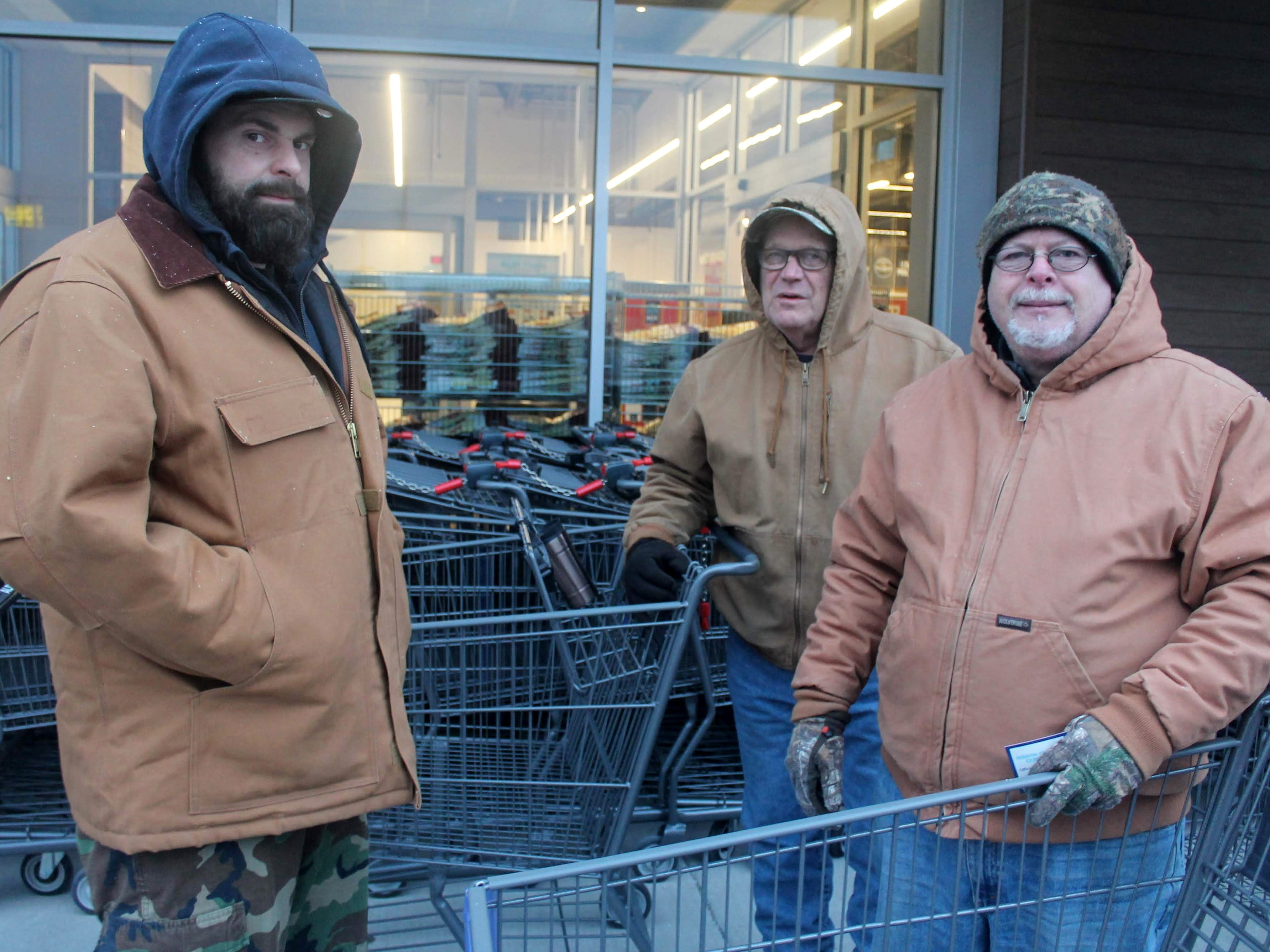 Livonia residents Rob Wagner, left, Jim McAllister, center, and Jim Marable, right, all wait in line to get into the new Aldi grocery store at Schoolcraft and Middlebelt in Livonia.