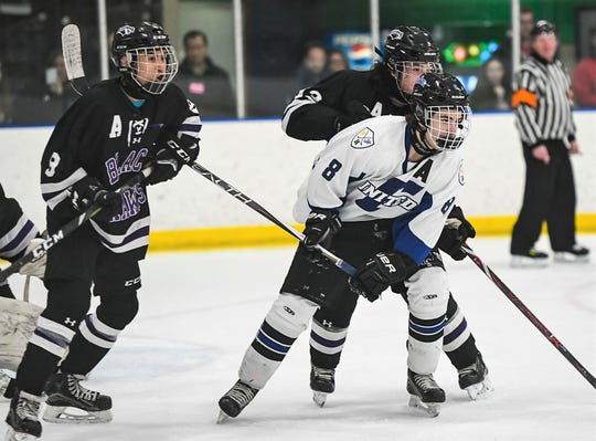 Farmington United's Ben Jugan (8) fights for position in front of the net with Bloomfield Hills player Dominic Yee (left) and Eddie Aguilar (top).