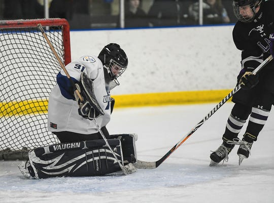 Farmington United netminder Nick Rogers (21) makes one of his 22 saves in a 7-2 win over Bloomfield Hills.