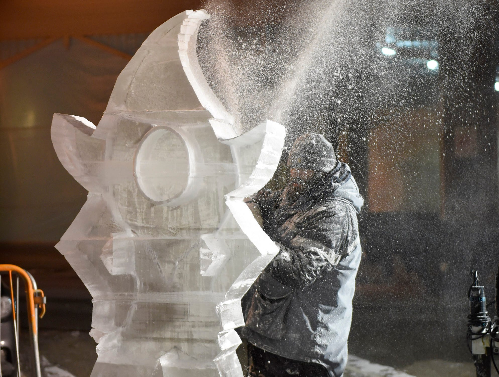 Jeff Meyers works on a carving Wednesday evening preparing for the Plymouth Ice Festival that runs Jan. 11-13.