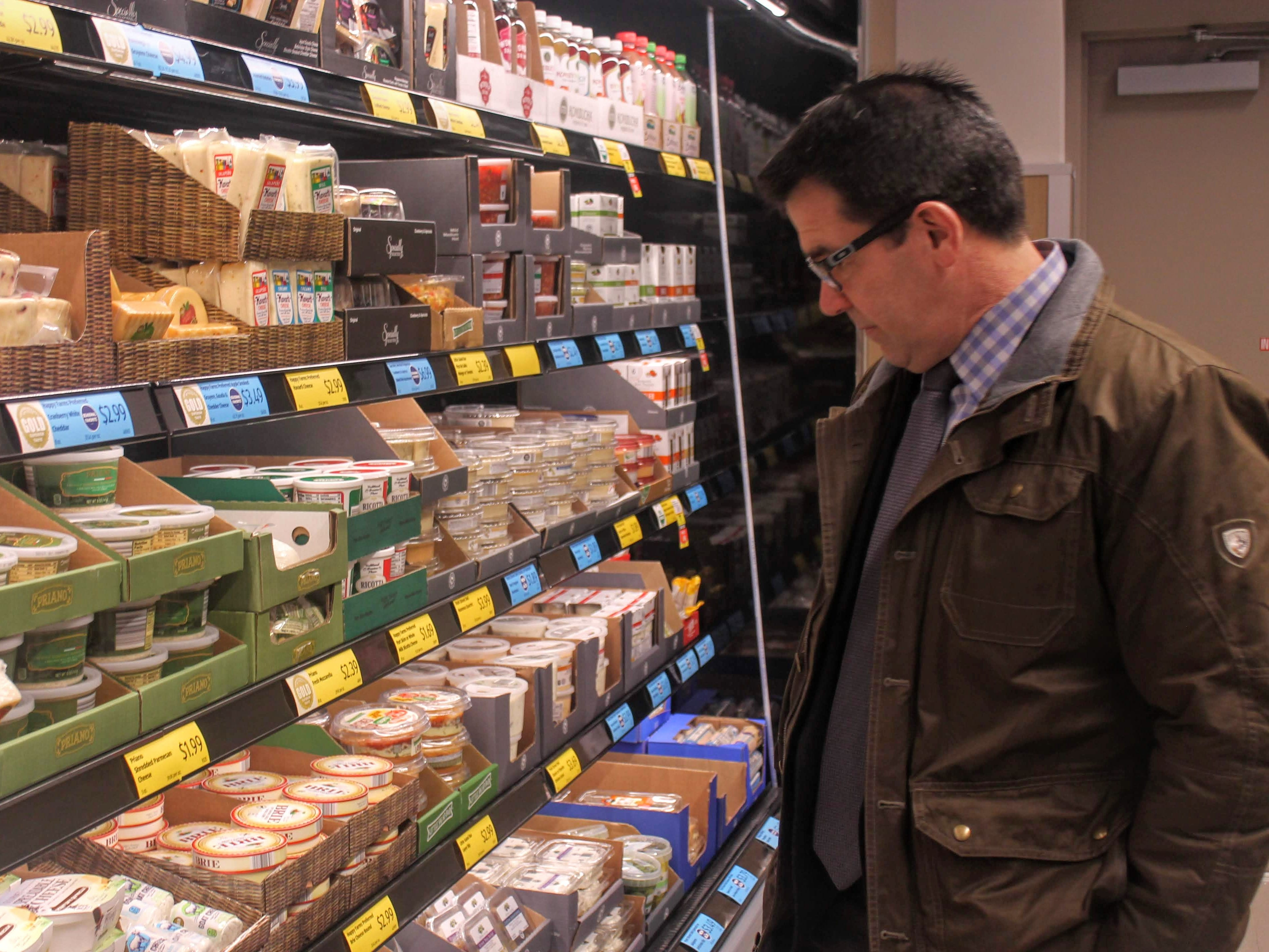 Mark Taormina, the city of Livonia's director of planning, looks at a selection of dairy in Aldi.
