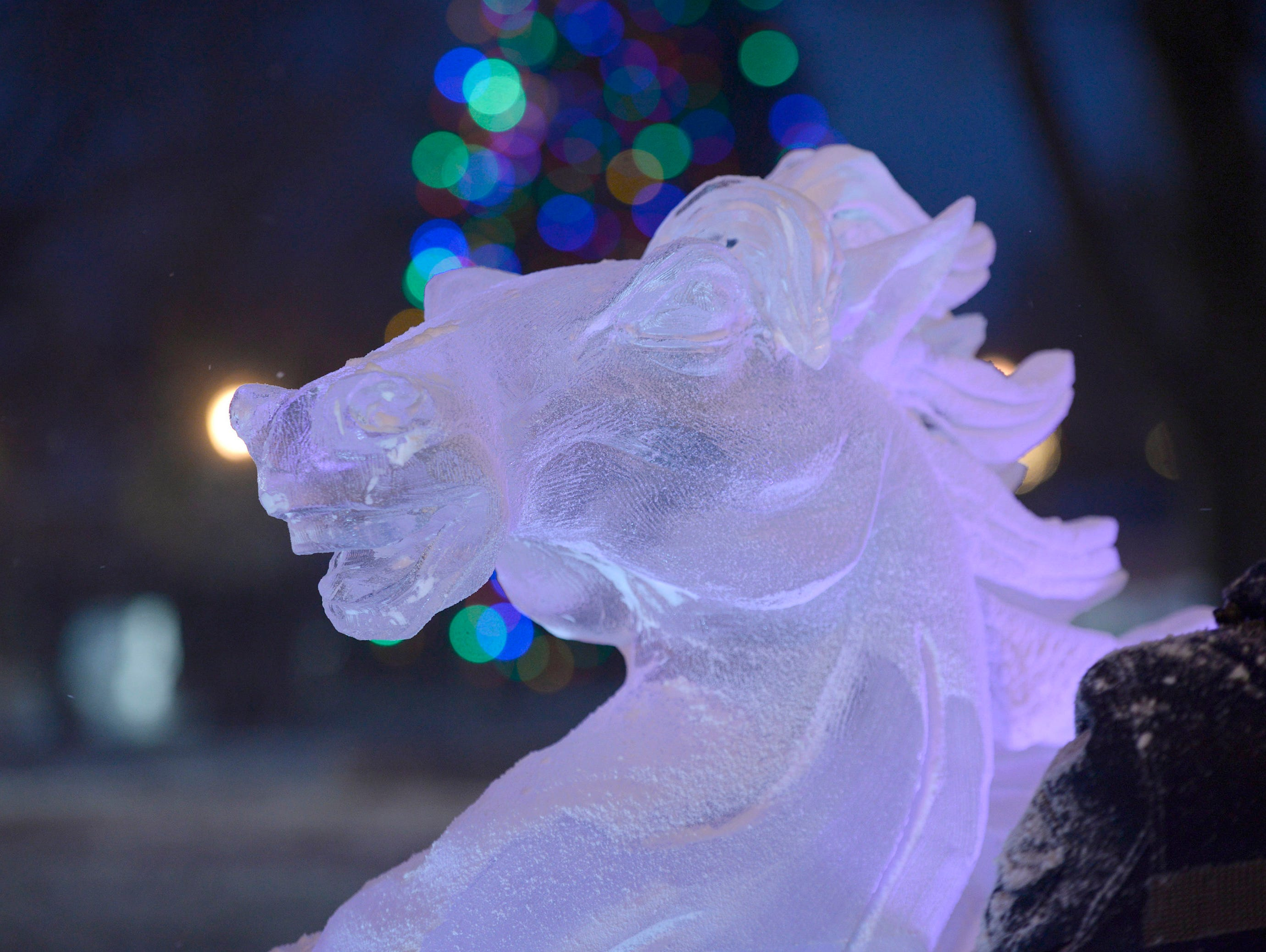 A carving is illuminated by the evening lights in Kellogg Park in downtown Plymouth.