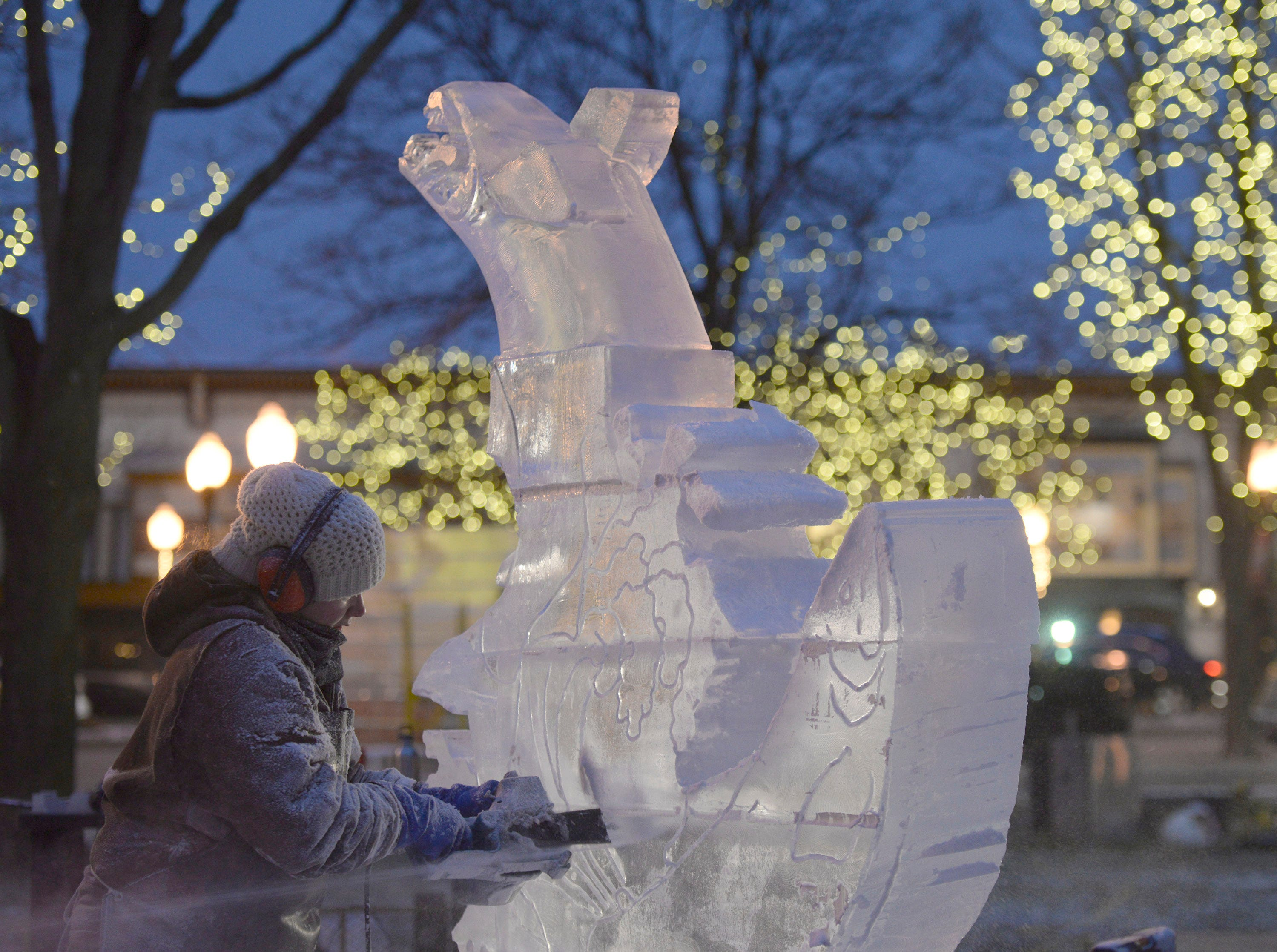 As Lauren Kaplar continues to carve into the evening, details emerge of the two salmon from the lights surrounding Kellogg Park in downtown Plymouth.