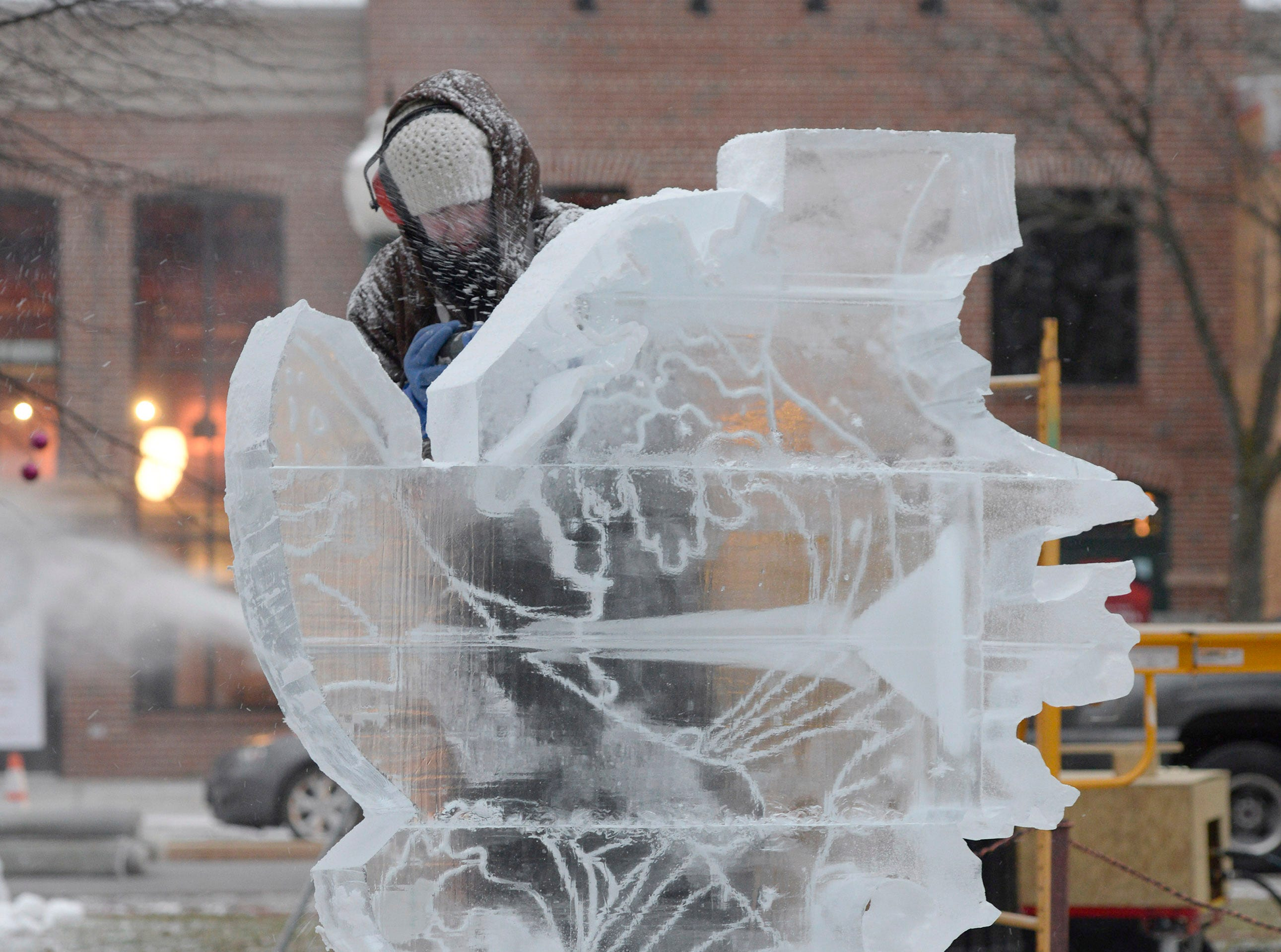 A sculpture featuring two salmon comes to life as Lauren Klapar works on a creation in Kellogg Park for the Plymouth Ice Festival that runs Jan. 11-13.