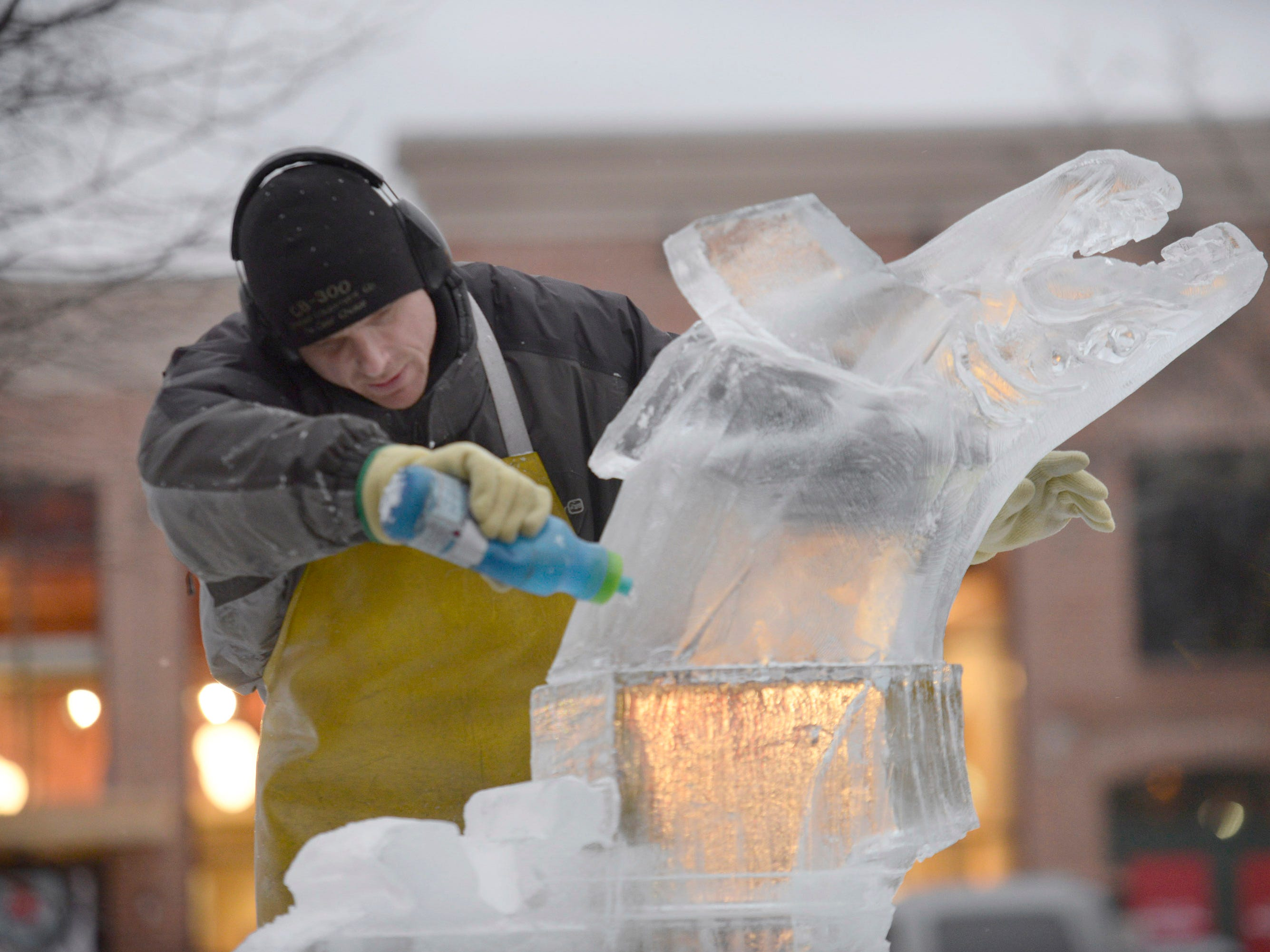 Clinton Rich from Clear Cut Ice uses water to seal an ice block carved into a salmon then moved to the top of other blocks of ice at the Plymouth Ice Festival that runs Jan. 11-13.