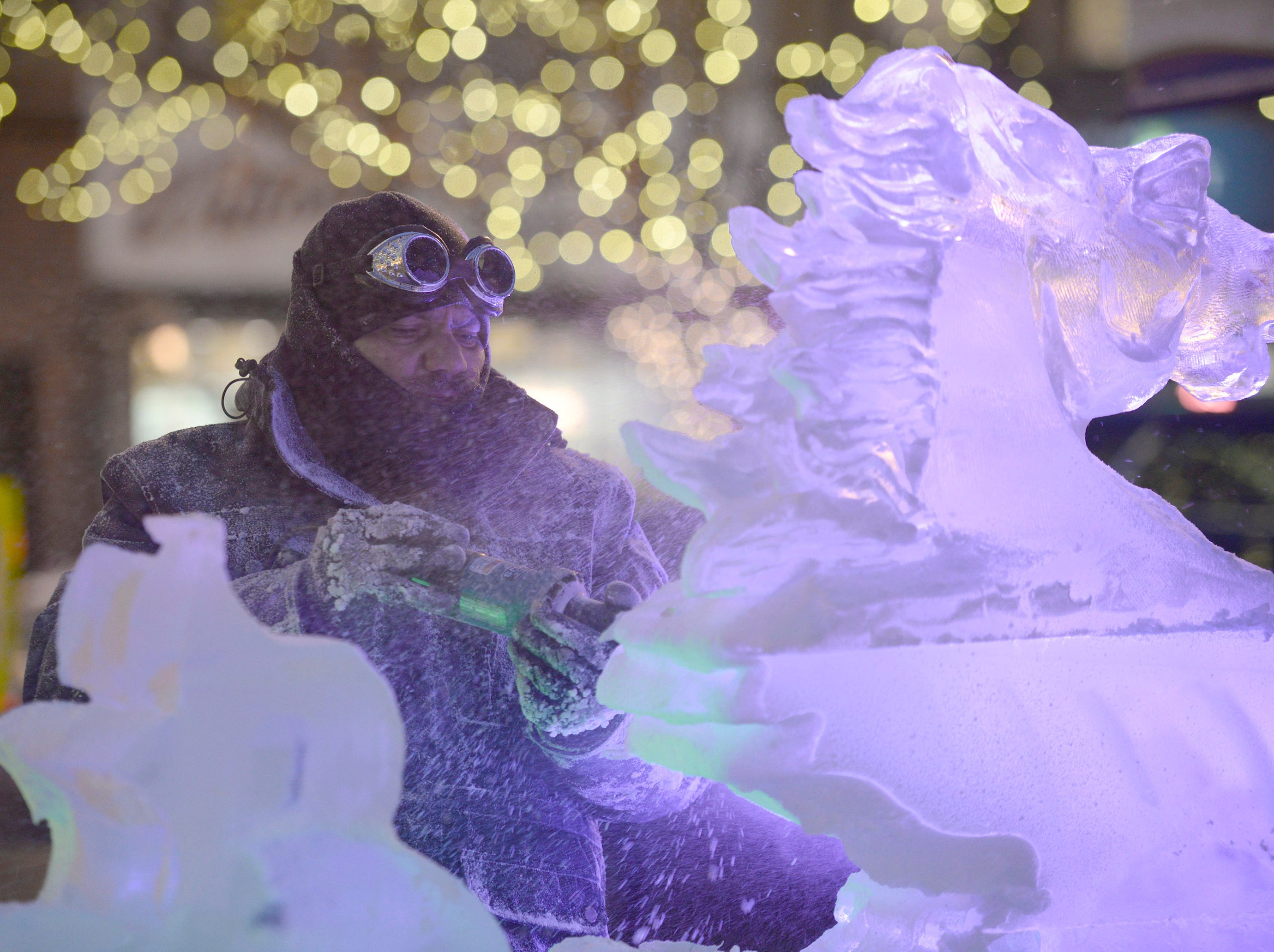 Evening lights illuminate the brilliance of the ice as sculptures start to emerge from blocks of ice at the Plymouth Ice Festival that runs Jan. 11-13. Here Max Zuleta works on a piece that will utilize 14 blocks of ice.