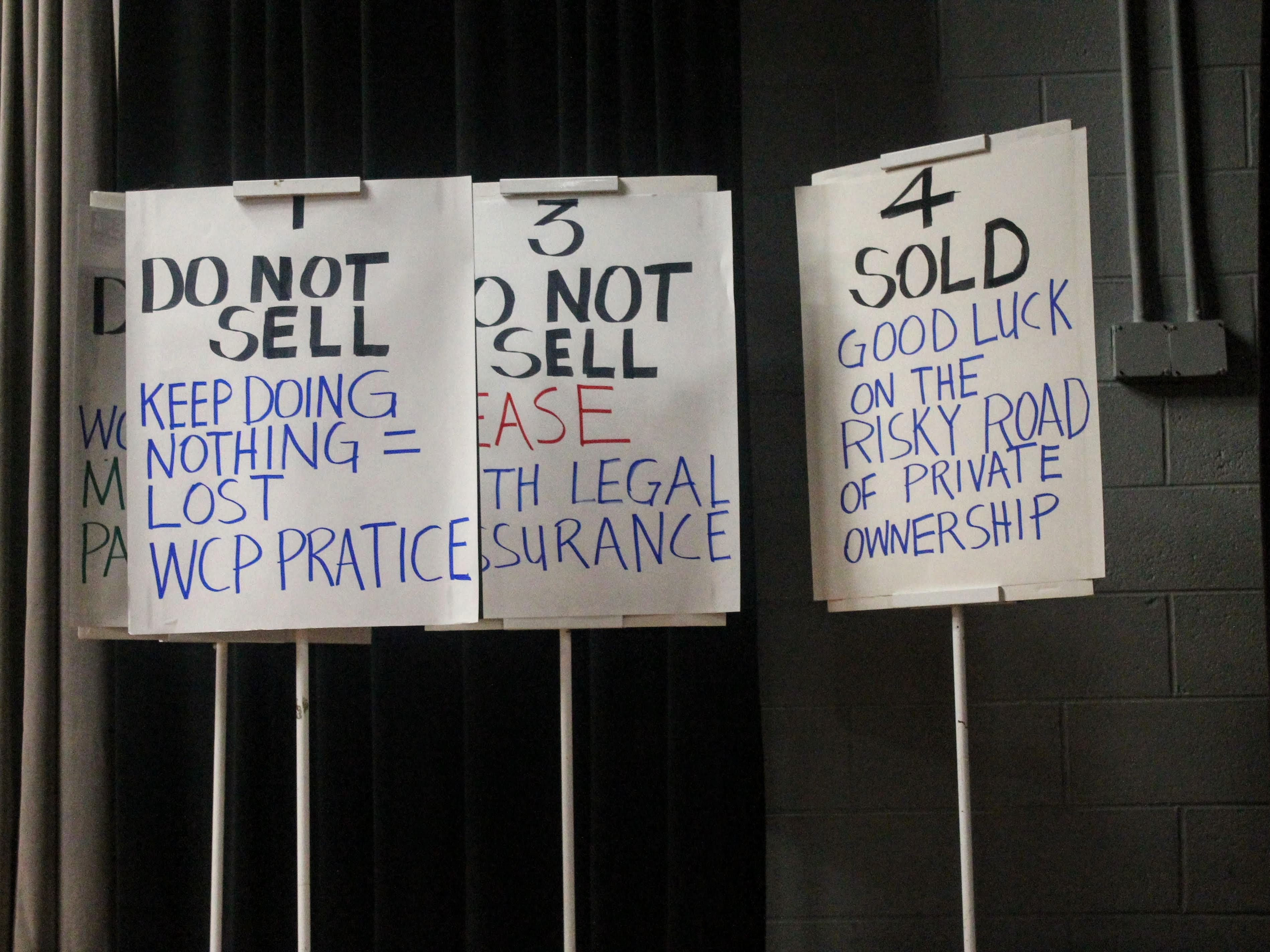 Signs on stage at the Save Hines Park meeting Jan. 9 at the Robert and Janet Bennett Library in Livonia.