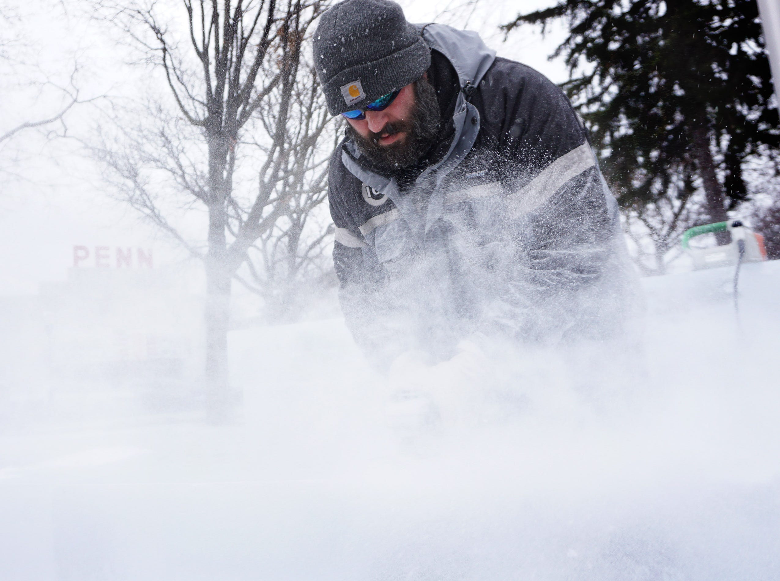 A cloud of flying ice dusts surrounds Jeff Meyers as he prepares blocks of ice for carving at the Plymouth Ice Festival that runs Jan. 11-13.