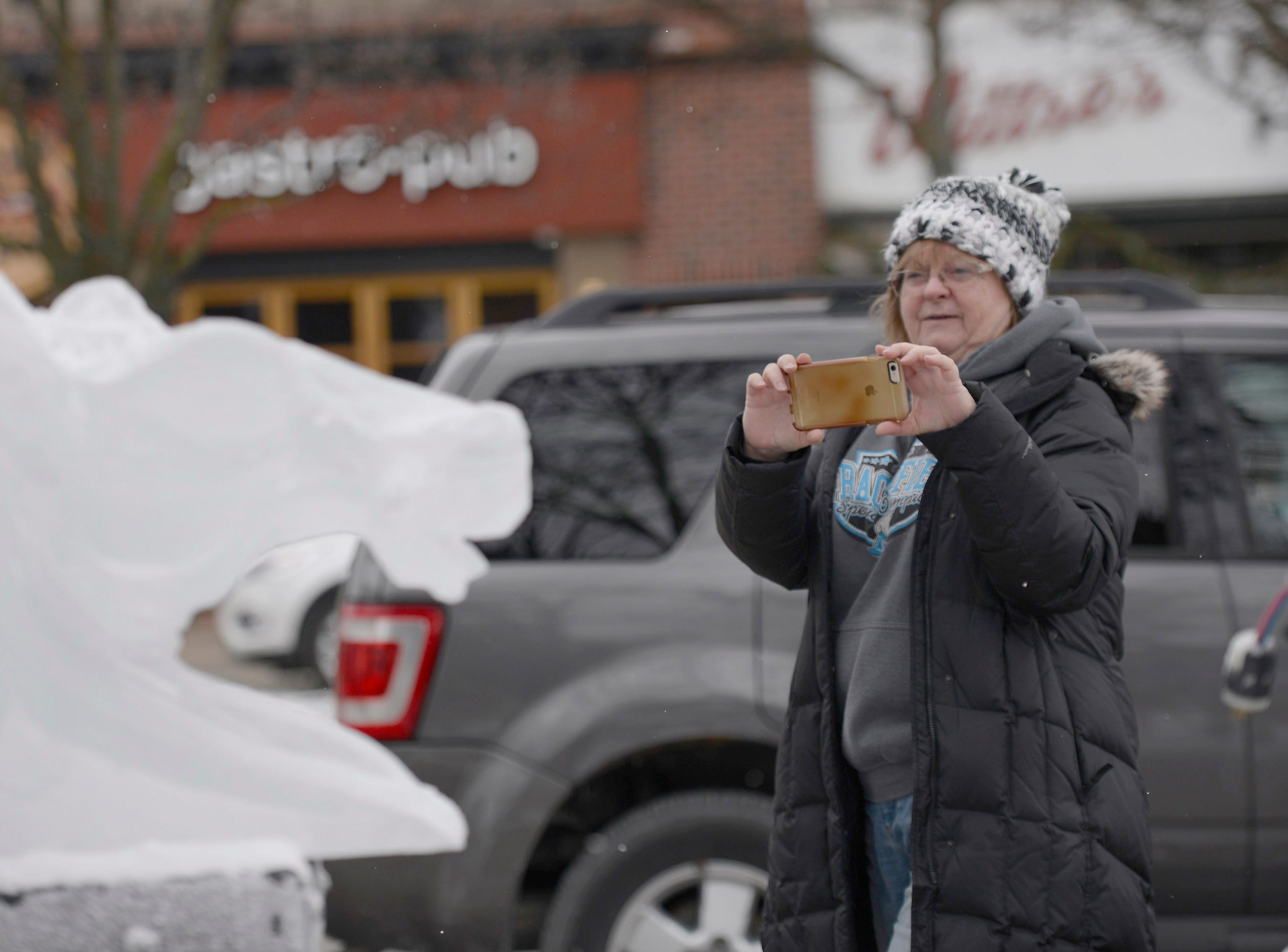 Debbie Lawless takes a photo of ice carvers preparing for the Plymouth Ice Festival on Jan. 9, 2019.