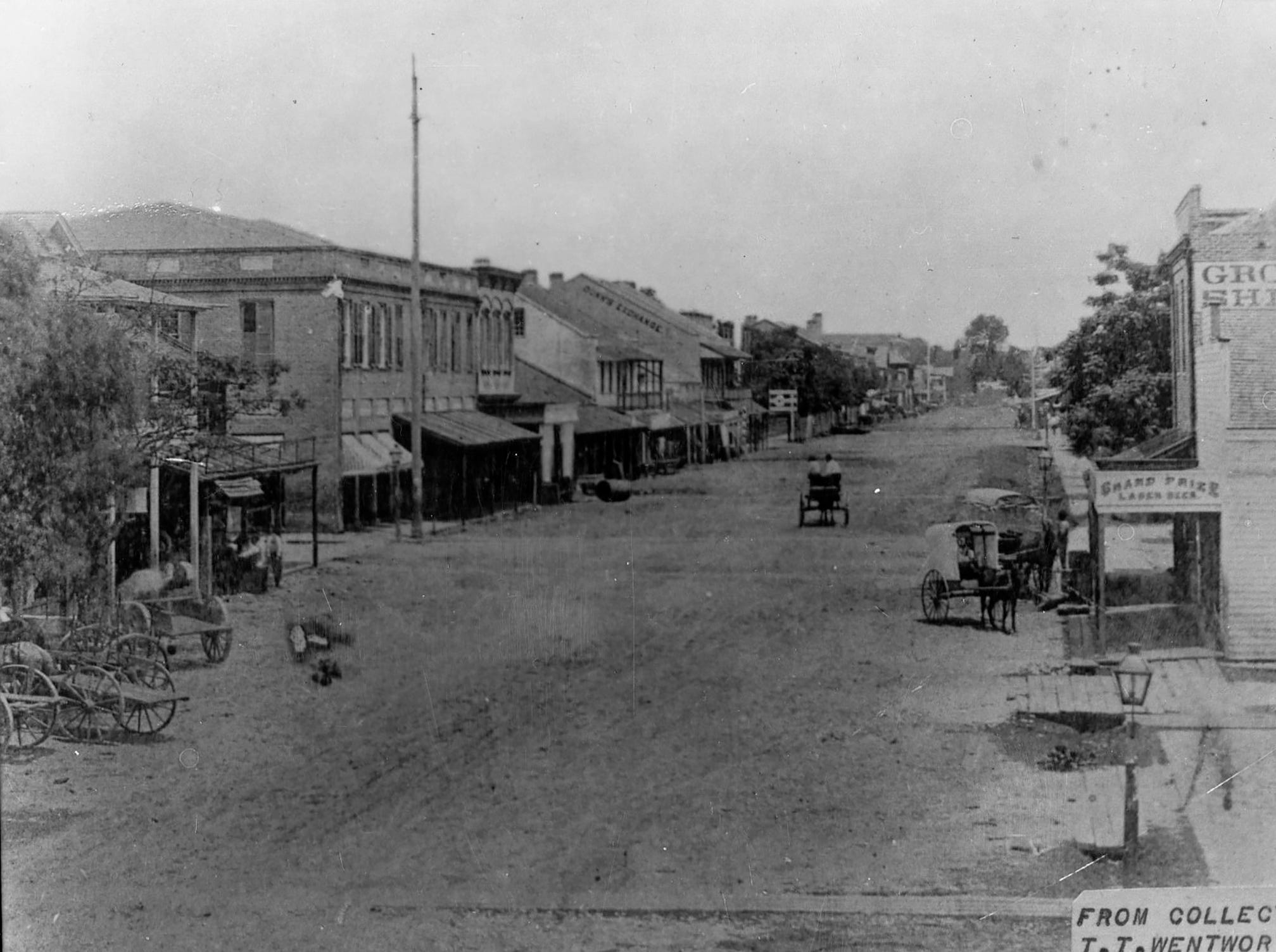 Palafox Street looking north, showing two-wheel horse-drawn carts on sandy streets, 1876.