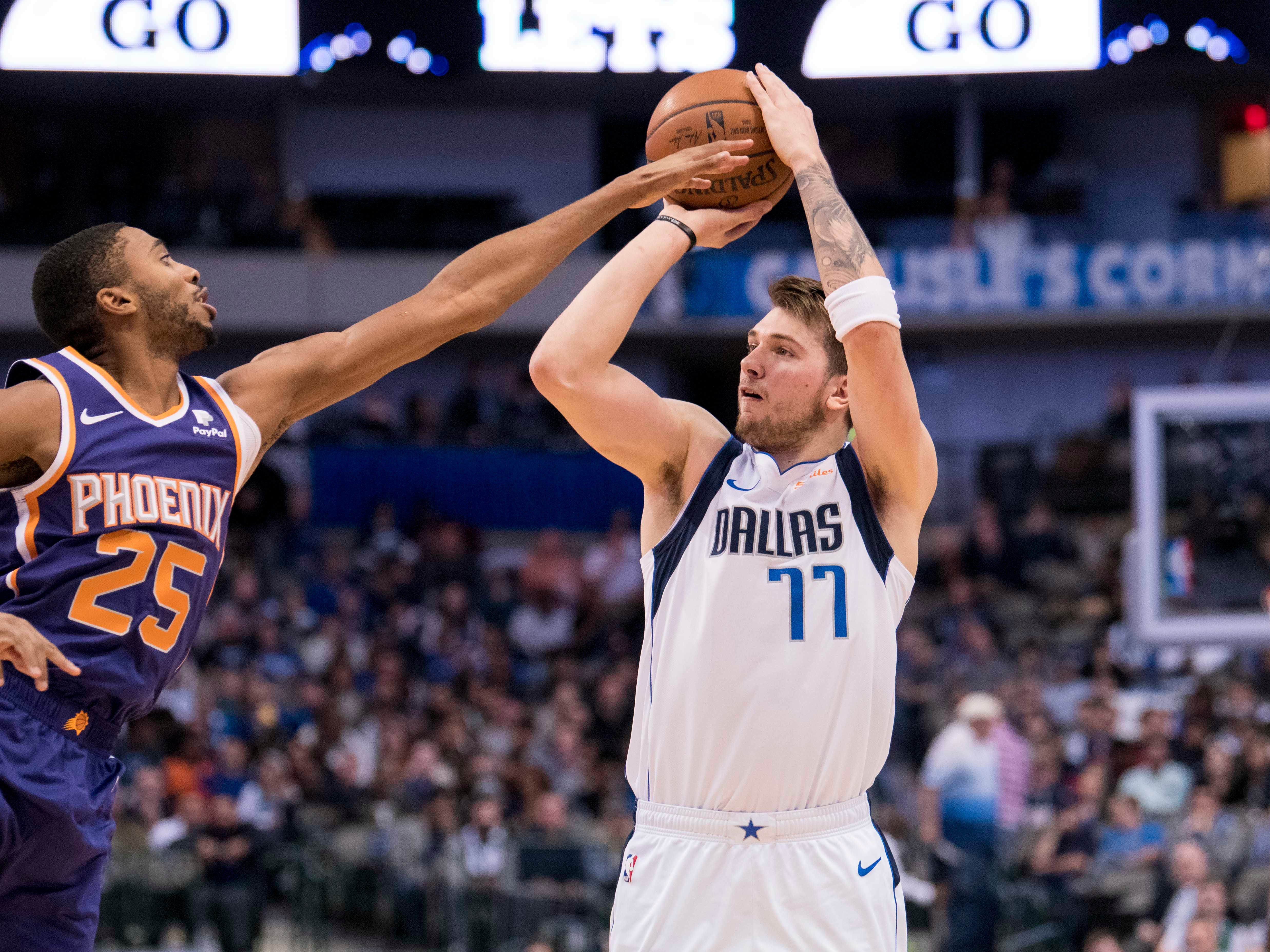Jan 9, 2019; Dallas, TX, USA; Dallas Mavericks forward Luka Doncic (77) is fouled by Phoenix Suns forward Mikal Bridges (25) on a three point basket during the first quarter at the American Airlines Center. Mandatory Credit: Jerome Miron-USA TODAY Sports