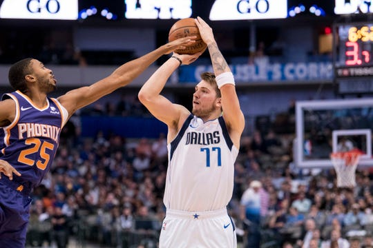 Mikal Bridges fouls Mavericks forward Luka Doncic during the first quarter of a game Jan. 9 at American Airlines Center.