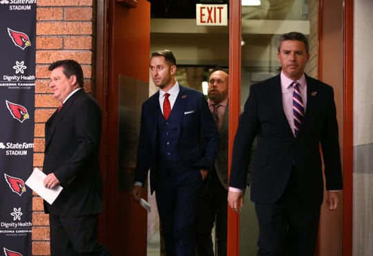 Kliff Kingsbury, center, arrives for his introductory news conference  on Jan. 9 as the new head coach of the Arizona Cardinals.