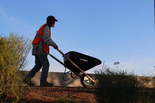 A participant of Glendale Works pushes a wheelbarrow at the Grand Canal Linear Park in Glendale.