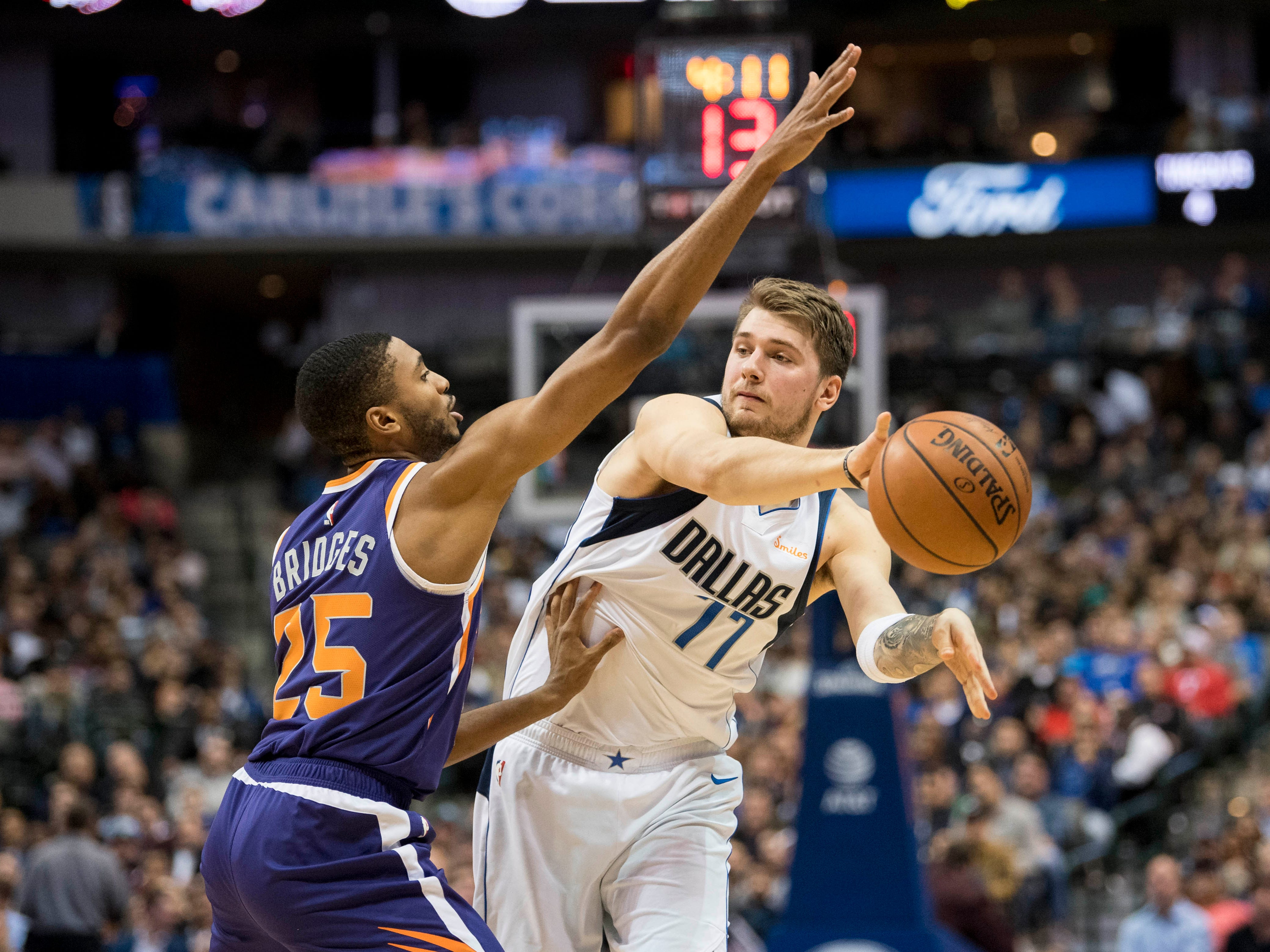 Jan 9, 2019; Dallas, TX, USA; Dallas Mavericks forward Luka Doncic (77) passes the ball around Phoenix Suns forward Mikal Bridges (25) during the second quarter at the American Airlines Center. Mandatory Credit: Jerome Miron-USA TODAY Sports
