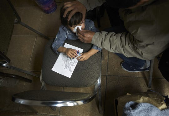 """In this Dec. 11, 2018, photo a man wipes his son's nose as he and other asylum-seekers listen to a volunteer after arriving from an immigration detention center to a shelter in San Diego. The American Dialect Society and the Linguistic Society of America have selected """"tender-age shelter,"""" meaning """"detention center for asylum-seekers child/children,"""" as the Word of the Year for 2018."""