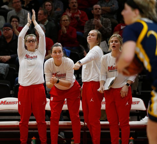 From left, injured Red Foxes Allie Best, Maura Fitzpatrick, Hannah Hand and Claire Oberdorf cheer on the Marist College women's basketball team against Quinnipiac on Thursday.