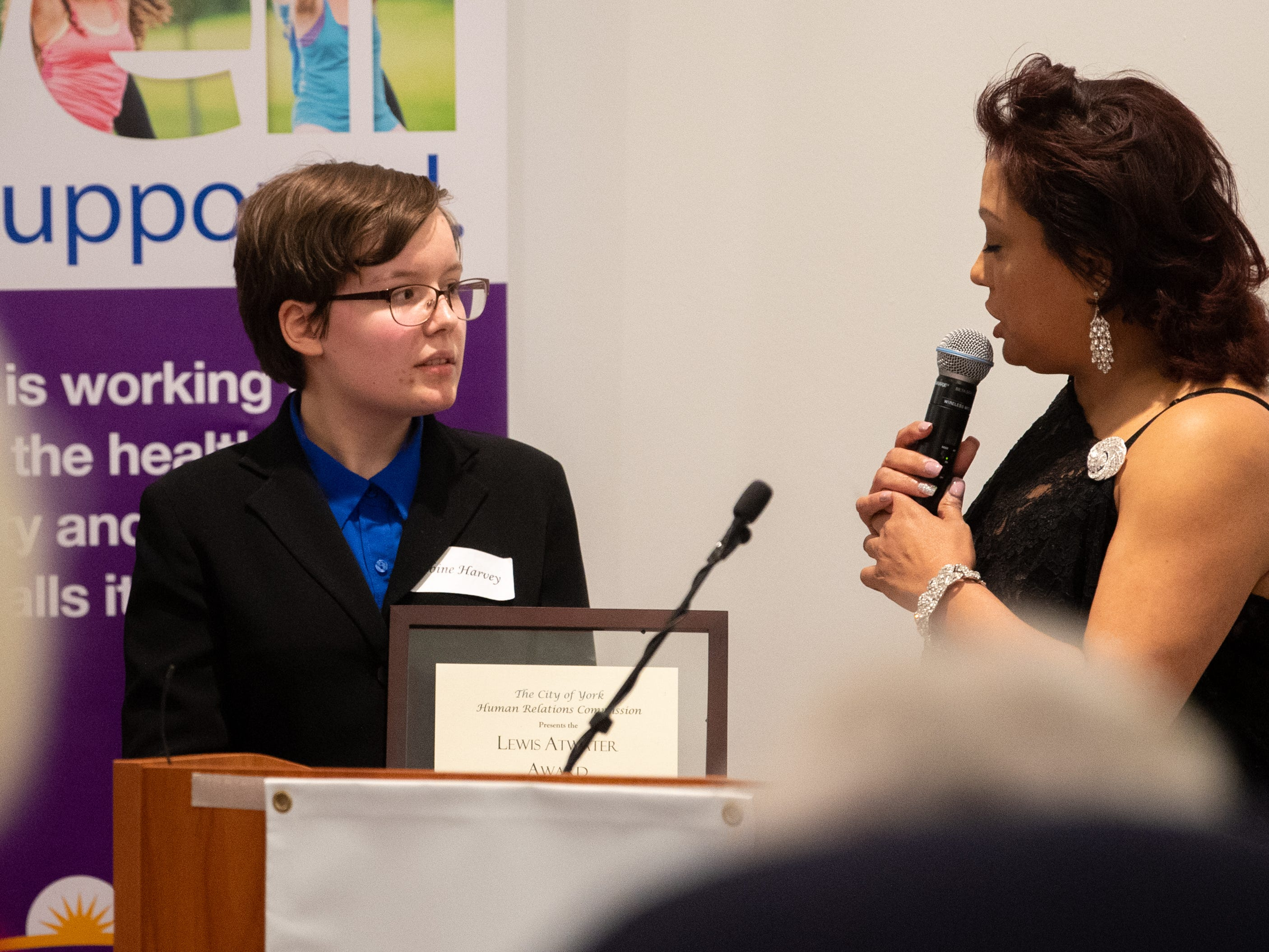 Lewis Atwater Award winner Sabine Harvey (left) listens intently to a recap of all her accomplishments during the 2019 City of York Human Relations Commission Diversity Dinner at York College, January 9, 2019.
