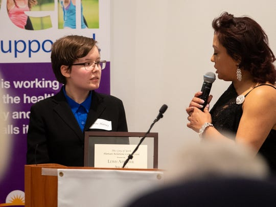 Lewis Atwater Award winner Sabine Harvey, left, listens to a recap of her accomplishments during the 2019 City of York Human Relations Commission Diversity Dinner at York College on Wednesday.
