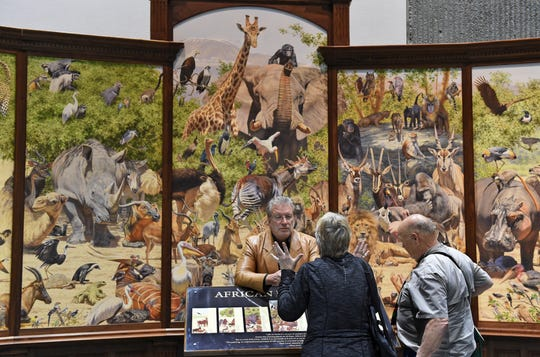Artist Brian Jarvi talks with SCI attendees as he stands in front of his 28 foot oil painting on opening day of the Safari Club International Convention at the Reno Sparks Convention Center on Wednesday Jan. 9, 2019.