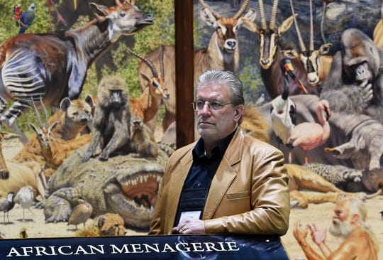 Artist Brian Jarvi stands in front of his 28-foot oil painting on opening day of the Safari Club International Convention at the Reno Sparks Convention Center on Wednesday Jan. 9, 2019.